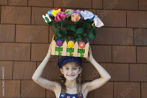 Portrait of little girl carrying artificial flowers in wooden crate on head