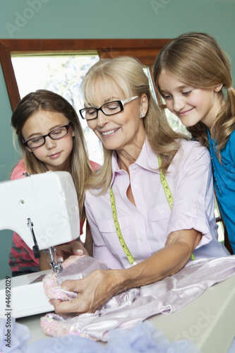 Girls looking grandmother sewing cloth