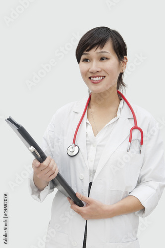 Young veterinarian holding report with stethoscope around neck over gray background