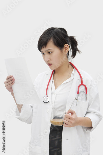 Asian female veterinarian reading document while having tea over gray background