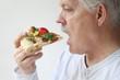 man eats BLT pizza profile view
