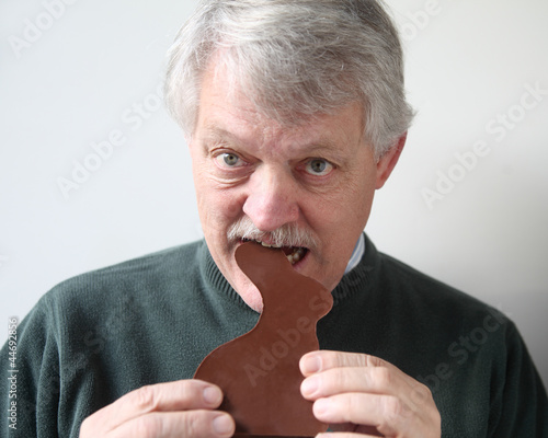 senior man bites into chocolate Easter rabbit