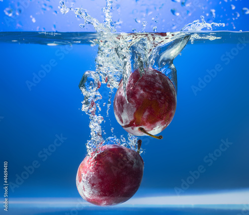 Fresh plums in water splash