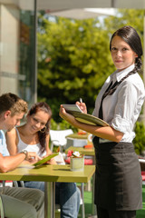Waitress waiting for clients to decide order