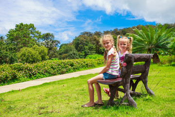 two happy sisters  sitting on the bench