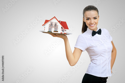 Waitress holding a tray with a house on it