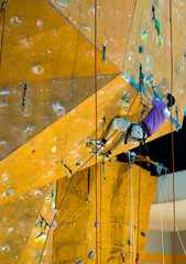 Climbing young adult to the top of wall