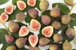 fichi freschi in composizione con foglie su tavolo bianco