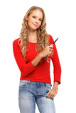 portrait of a pretty blond woman pointing with pen at copyspace