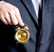 Business man holding a golden clock