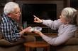 Senior couple arguing over TV remote control