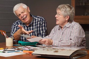 Senior couple choosing photos for album