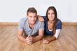 Cute young couple laying on wooden floor