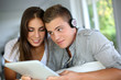 Young couple listening to music on electronic tablet