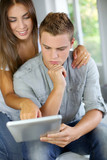 Young couple websurfing on electronic tablet