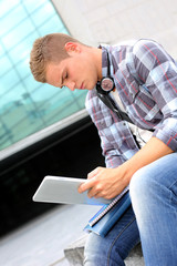 University student using digital tablet and headphones
