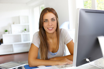 Beautiful office worker sitting in front of desktop