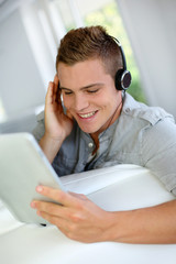 Young man listening to music with digital tablet