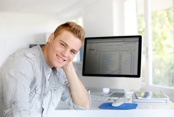 Portrait of young man sitting in front of computer