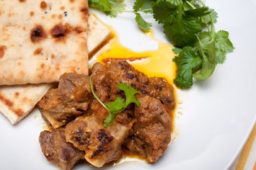 Lamb curry cirrander and Naan close up on a white plate