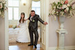Groom pulling bride through the door for wedding ceremony