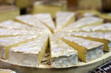 Brie cheese round, sliced on a plate, landscape