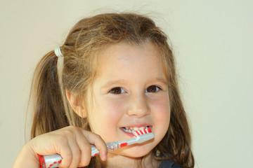 smiling girl washing her white teeth using a toothbrush an