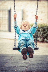 Little Boy Playing on the Swing