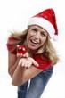 Blonde Frau mit Weihnachtsmütze und roter Christbaumkugel