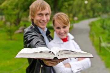 Two students with open book in the park. Focus on book