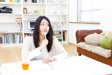 a young asian woman studying in the room