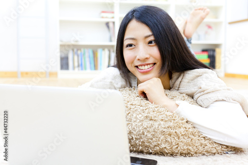 a young asian woman using laptop in the room