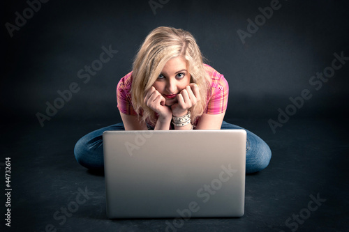 Pretty girl working on a laptop against black background.