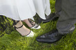 bride and groom legs over the green grass