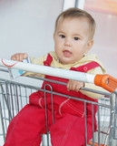 cute baby child in shopping cart in supermarket