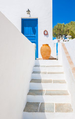 Staircase and ceramic vase near blue door, Sifnos, Greece