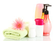 cosmetics bottles with towels and flower isolated on white