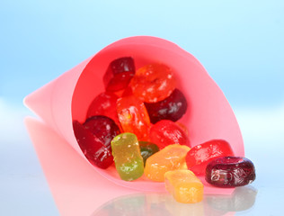 Tasty colorful candies in bright bag on blue background
