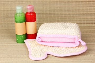 Bottles with scrub and sponges on bamboo background
