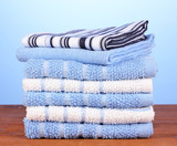 kitchen towels on wooden table on blue background close-up