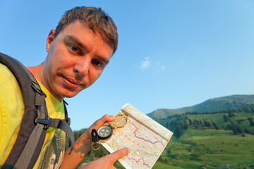 Tourist with a map and compass in the mountains of Switzerland.