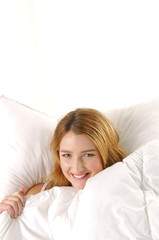 Happy young woman in bed