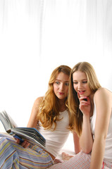 Beautiful two young women reading book on bed