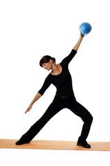 Frau mit Ball macht Gymnastik