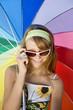 Teenage girl under iridescent  umbrella