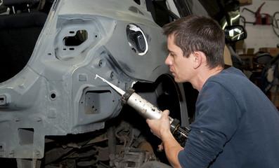 worker sealing a car body.