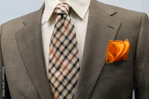 Light grey checkered jacket with brown checkered tie and orange