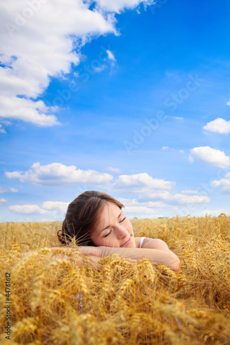Pretty woman on yellow wheat field
