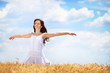 Young woman having joy in wheat field