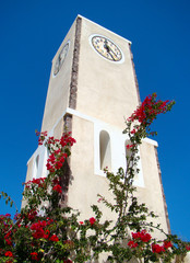 Clock tower surrounded by flowers and blue sky